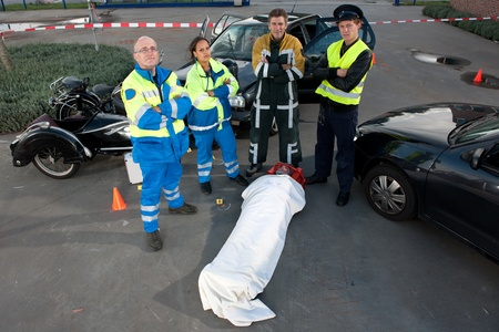 Emergency Medical Services team posing over an injured driver at the scene of a car crash photo