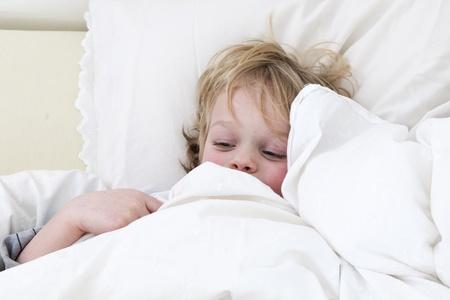 cuddled: Sick boy, cuddled up under the duvet in his bed.