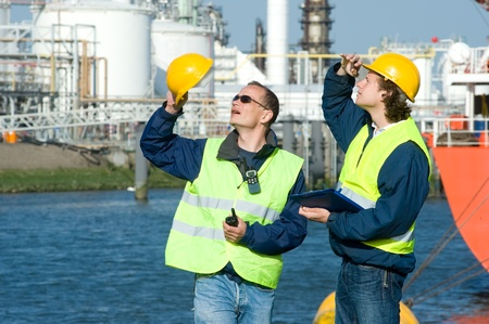 inspection: Two dock workers at inspection, looking up. Stock Photo