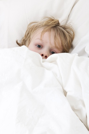 fear child: Young child, lying awake in his bed, with his eyes wide open, covering himself up, scared from the nightmare he just had Stock Photo