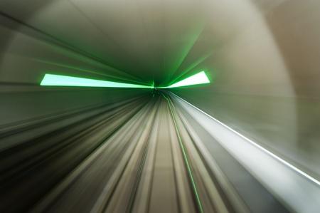 salidas de emergencia: Imagen dinámica de un tren, conduciendo a través de un túnel de metro con bengalas verdes que indica las salidas de emergencia, iluminado con luces de cabeza.