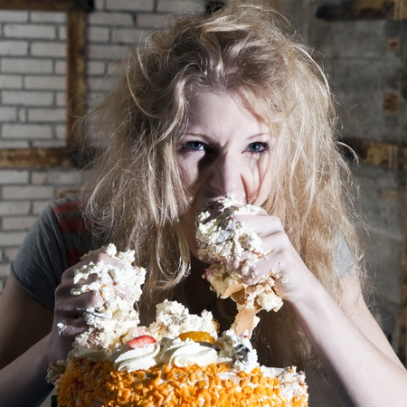 unkept: Young woman, ravaging a cake with both hands, eating uncontrollably