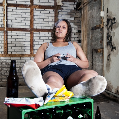 Lazy woman, in an unkept room, looking sleazy with a cigarette in her mouth, playing video games photo