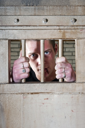 Prisoner with a split lip holding the bars of his jail cell door Stock Photo - 9295583