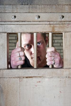 cellule prison: Prisonnier avec une l�vre fendue tenant les barreaux de la porte de sa cellule de prison