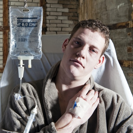 the dying: Very sick man, with an IV drip sitting in a chair