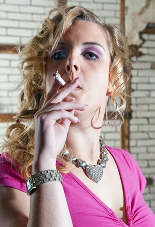 top seven: Vain, over the top dressed woman smoking a cigarette, and looking arrogant Stock Photo