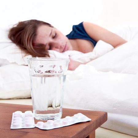 bedside: Vaso de agua y dos tiras de p�ldoras en una mesita con una mujer enferma durmiendo en segundo plano Foto de archivo