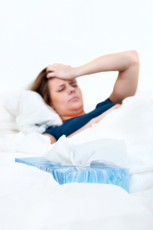 handkerchiefs: Tissue box in between the sheets, with a young woman, suffering from a severe headache, lying in bed, sick
