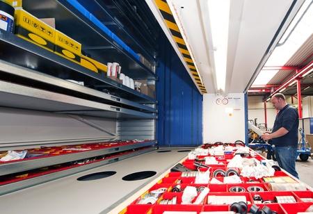 shelfs: Mechanic entering the tray number of a automated storage shelfs