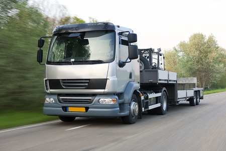 Truck and trailer combination, carrying a forklift, driving at speed  photo