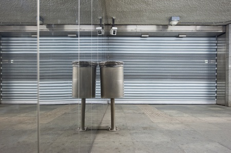 close circuit camera: Trash can and closed store front shutters along a mirror wall in a deserted subway station Stock Photo