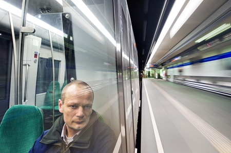 Man, sitting in a metro at night, passing a station, looking out the window with a weary  and tired look in his eyes photo