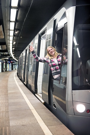 Young woman waving from the drivers compatiment of a subway train, standing stationary at a platform photo