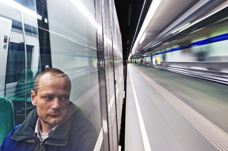 Lone man sitting in the subway on his way home passing a deserted station photo