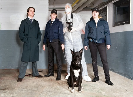 Crime scene investigation team, with an inspector, two uniformed police with a police dog and a forensic detective photo
