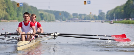 rowing boat: Oarsmen building up speed during a rowing race Stock Photo