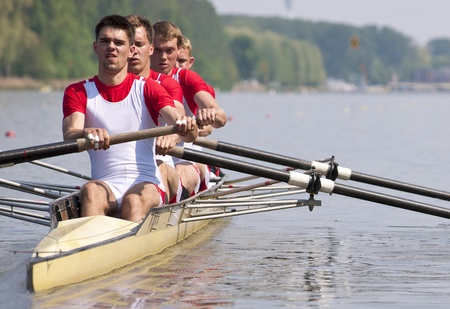 rowing boat: Coxed four rowing team during the first strokes after the start of a race