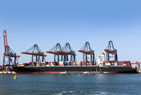 commerce and industry: Container ship being unloaded at an industrial harbor