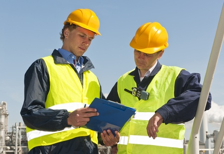 Dos ingenieros petroquímicos vistiendo chalecos de seguridad y un techo duro en una lista de comprobación