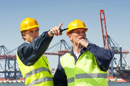 cb: Two dockers in discussion, in front of a large industrial harbor