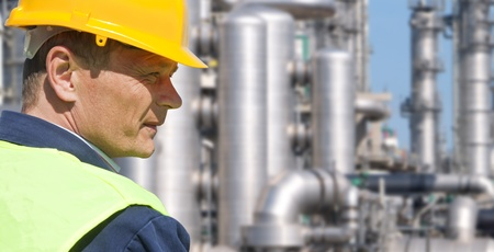 oil and gas industry: Close up of an engineer wearing a safety vest, blue coveralls, and a hard hat in front of a petrochemical plant