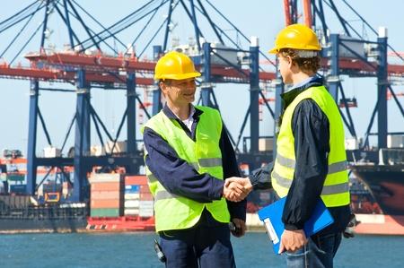 export and import: Dos de los cargadores de muelle estrechan la mano de un puerto industrial con gr�as y un barco de contenedores se descarga