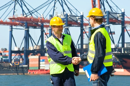 ports: Two dockers shake hands in front of an industrial harbor with cranes and a container ship being unloaded