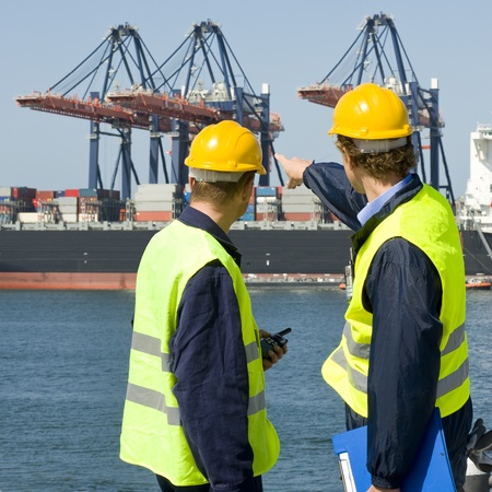 containerschip: Two dockers in discussion, pointing at the unloading operations of a huge container ship