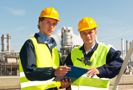 hardhat: Two engineers, wearing reflective clothing and a hard hat, looking up from the note board they have been discussing