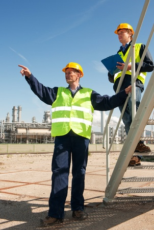 A worker discussing procedures with another worker in front of a petrochemical refinery photo