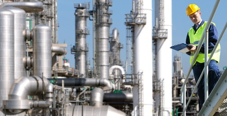 refineries: A petrochemical engineer, with a noteboard in his hand in front of a huge refinery Stock Photo