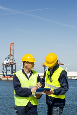 noteboard: Two dockers discussing procedures and plans at the waters edge