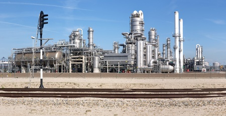 petrochemical plant: A petrochemical plant, with its stainless steel cylinders, its valves, chimneys, pipes, tubes and construction with a railway and signpost in front. Stock Photo