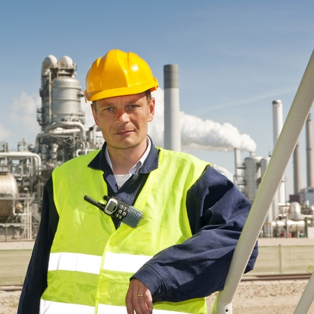 petrochemistry: Engineer poses casually in front of a refinery, wearing a safety vest and hard hat
