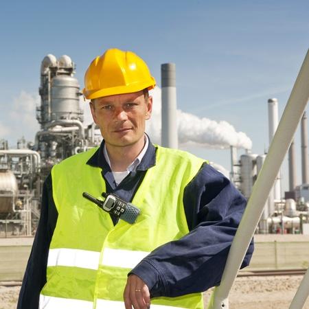 petrochemistry: Ingeniero poses casualmente en frente de una refiner�a, llevaba un chaleco de seguridad y cascos