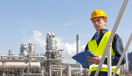 petrochemical plant: Young supervisor with a note board and pen in his hands, wearing a hard hat and safety vest in front of a petrochemical plant and refinery