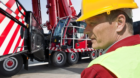 Man, wearing a hard hat and reflective vest in front of his huge mobile crane Stock Photo - 9679861