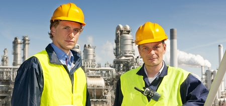 petrochemistry: Two petrochemical engineers in front of a refinery, wearing hard hats and safety vests Stock Photo
