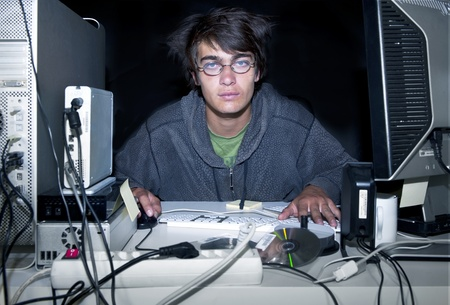 Man, sitting behind a small desk, stacked with computer gear, committing cyber crime. The cyber criminal at work Stock Photo - 9763348