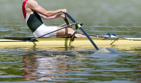 Close up of a muscular skiff rower during the first strok of a regatta Фото со стока