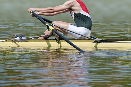 competitive: Skiff rower explodes into action at the starting signal of a rowing match