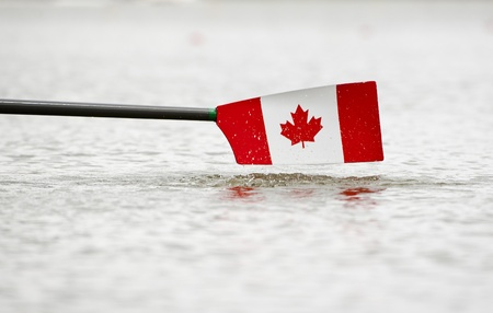oars: Rowing oar and blade in the colors of Canada, hovering just above the water