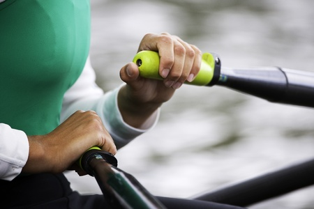 rowing: Close up of hands and oar handles of a womans single sculls rower