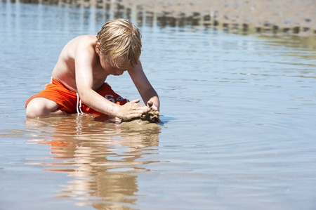 Young child plays with sand in the shallows of a beach on a beautiful summer day Stock Photo - 10097574
