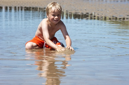 swimming shorts: Young boy plays with sand in the shallows of a beach, and smiles in the camera Stock Photo