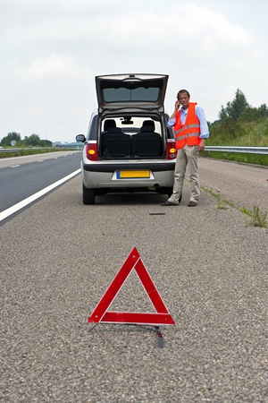road assistance: Broken down car at the side of the road, with a man, wearing a reflective vest calling for assistance, a warning triangle. proper procedrue of road safety