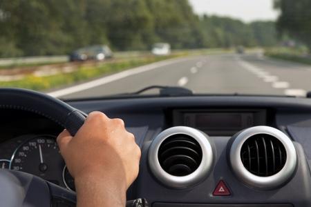Conduire une voiture avec une main sur le volant Banque d'images