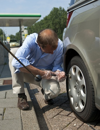inflating: Man, inflating a tire and checking for the proper air pressure in the wheels of his car Stock Photo