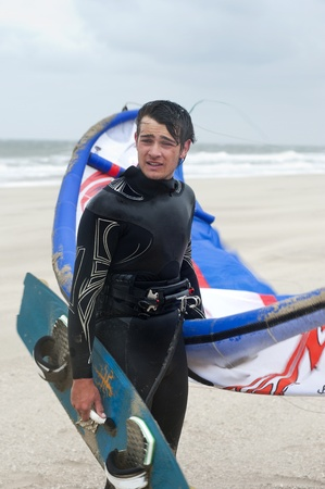 Kite surfer wearing a wetsuit on the beach on a windy day, holding his board and kite, looking sideways photo